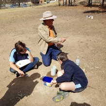 2 students from Uralla Central School doing a water infiltration experiment with one of our executive members.
