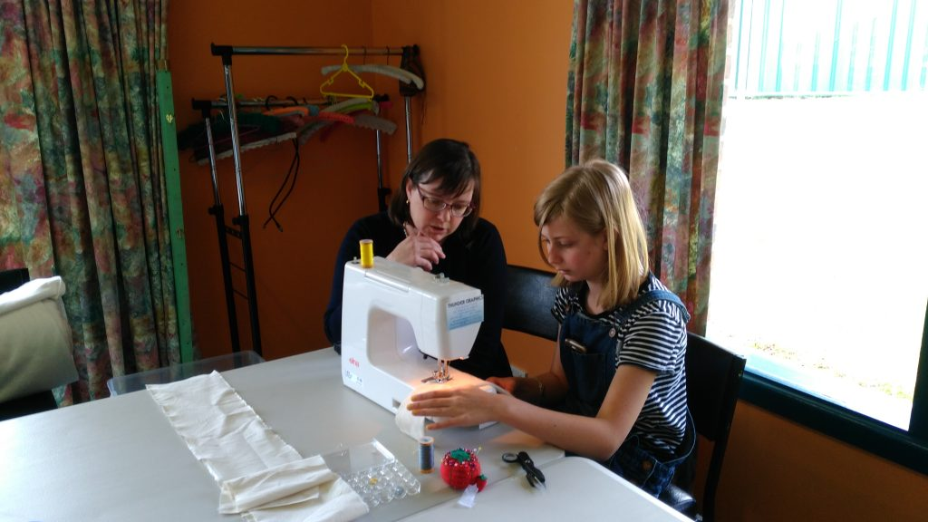 A younger student being shown how to use the sewing machine