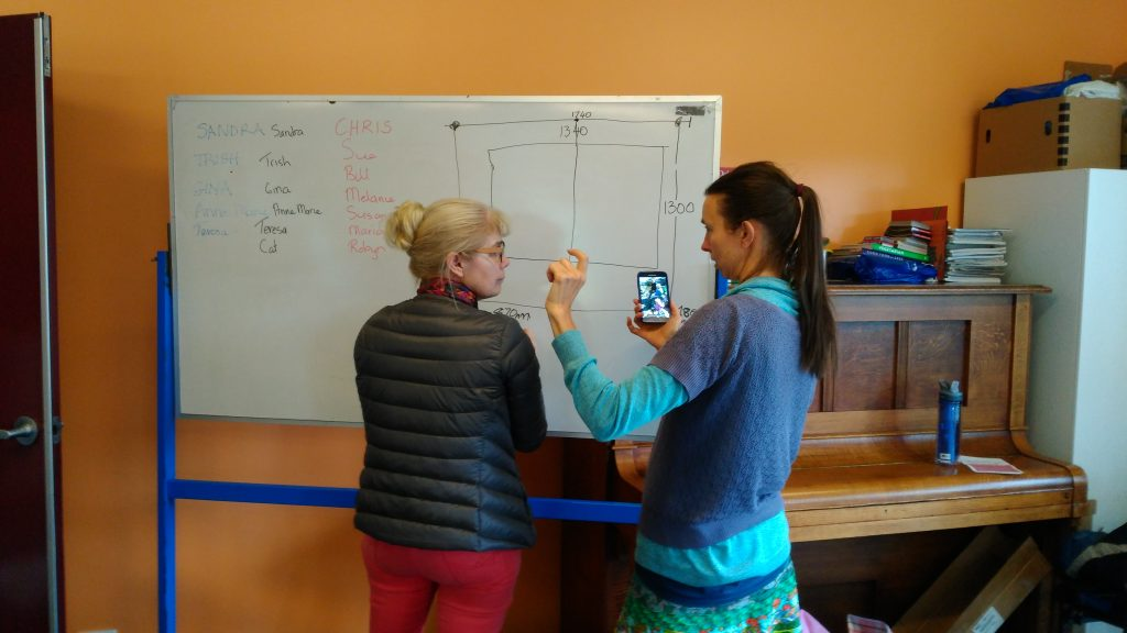 One of the participants getting advice on measurements for curtain with diagrams on whiteboard of window dimensions