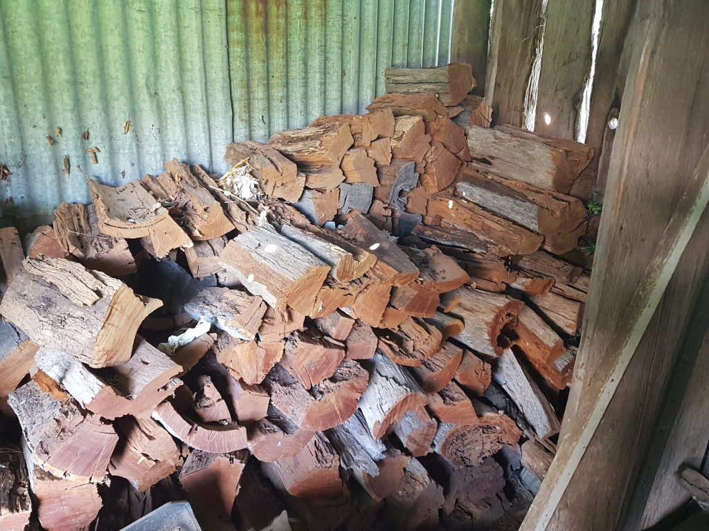Cut wood stored in a wood shed to keep dry